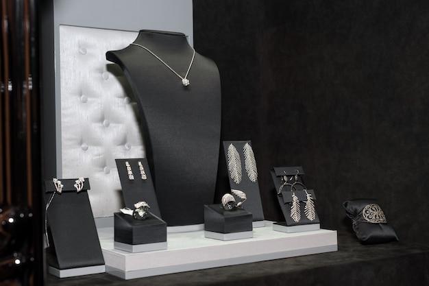Variété De Bijoux En Vitrine. Vente De Bagues, Bracelets, Boucles D'oreilles Et Colliers Sur Des Supports. Photo Premium
