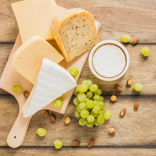 Variété de blocs de fromage avec des raisins; amandes et châtaignes sur un bureau en bois Photo gratuit