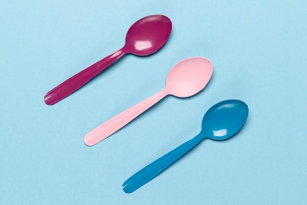 Variété de cuillères colorées sur fond bleu Photo gratuit