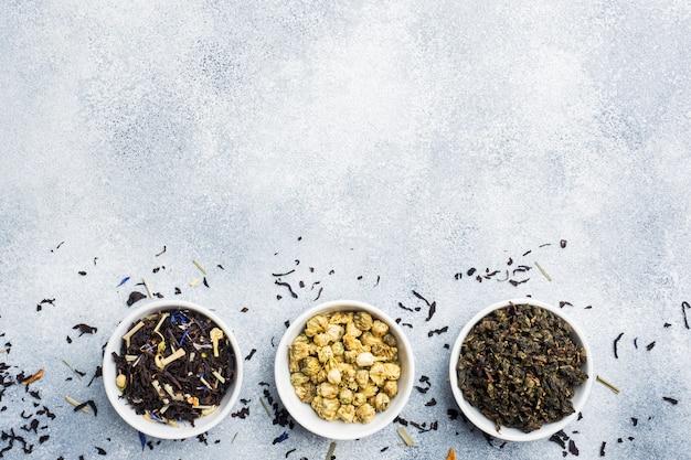 Variété de feuilles de thé séchées et de fleurs dans un bol sur fond gris. Photo Premium