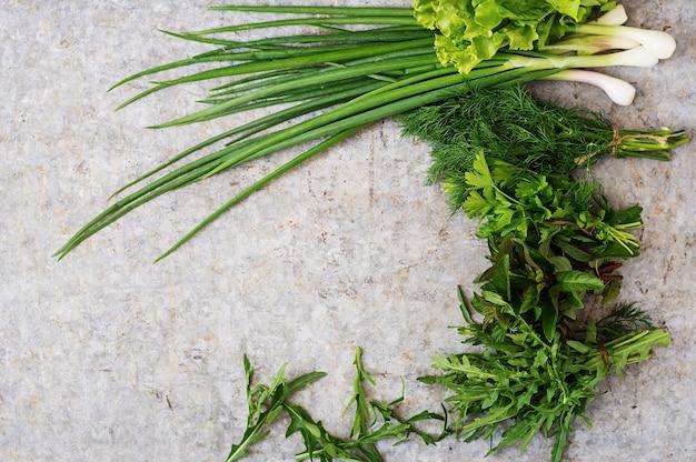 Variété D'herbes Biologiques Fraîches (laitue, Roquette, Aneth, Menthe, Laitue Rouge Et Oignon) Sur Fond Gris Dans Un Style Rustique. Vue De Dessus Photo gratuit