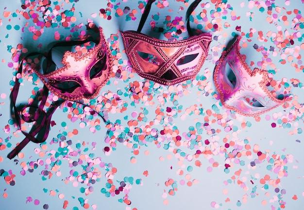 Variété de masque pour les yeux du parti avec des confettis colorés sur fond bleu Photo gratuit
