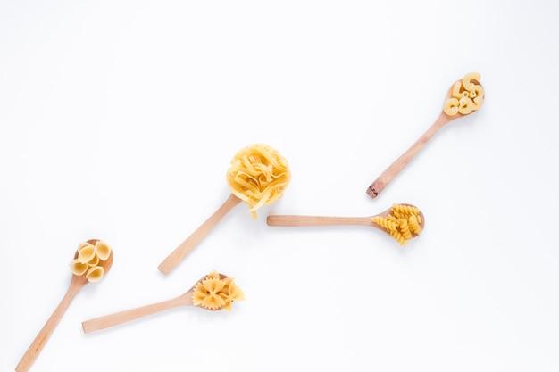 Variété de pâtes italiennes de blé entier non cuit sur une cuillère en bois, isolée sur fond blanc Photo gratuit