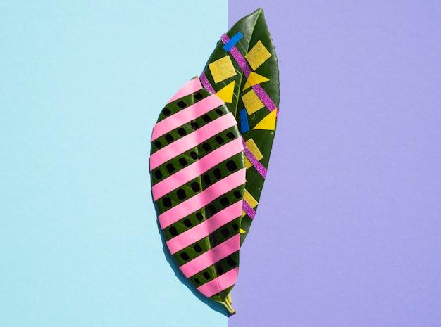 Variété de peintures et d'articles de papeterie sur des feuilles de ficus Photo gratuit
