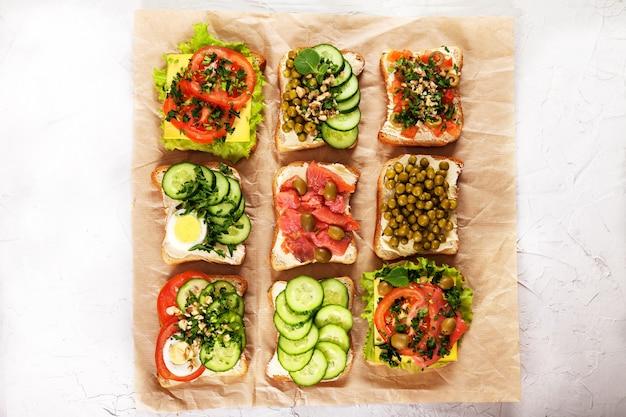 Une Variété De Sandwichs Avec Du Fromage à La Crème, Du Saumon, Des œufs, Des Herbes Et Des Légumes Sur Du Papier Kraft Photo Premium
