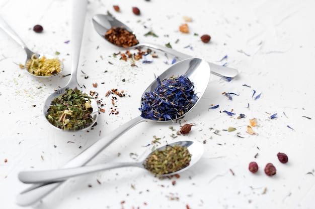 Variété De Thé Séché, De Fines Herbes Séchées, De Thé Vert Et De Fruits Sur Des Cuillères. Photo Premium