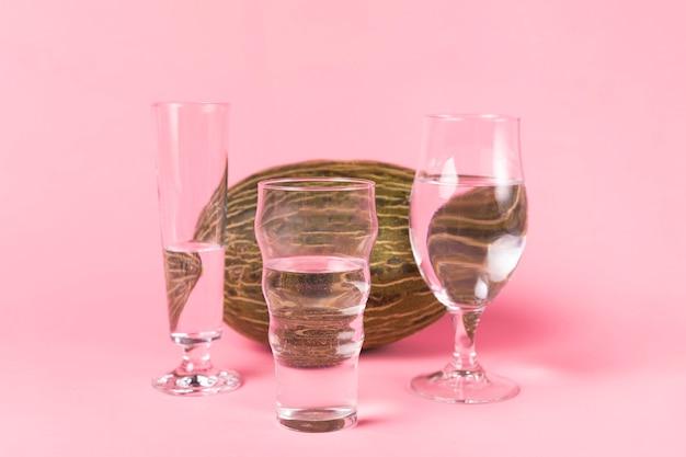 Variété de verres à eau et de melon Photo gratuit