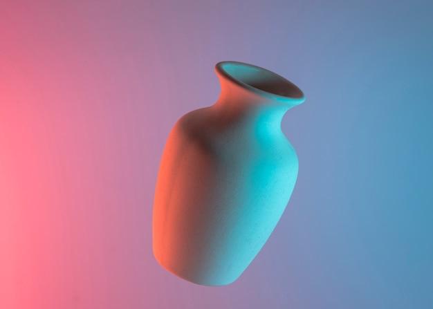 Vase blanc en céramique dans l'air sur un fond coloré de bleu et de rose Photo gratuit