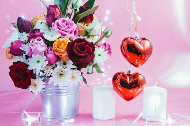 Vase de bouquet roses, coeur rouge et bougie blanche Photo Premium