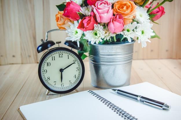 Vase bouquet roses près de l'horloge vintage et cahier Photo Premium