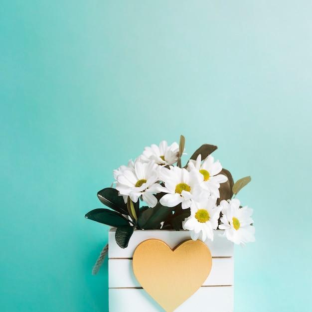 Vase à fleur en forme de coeur sur fond turquoise Photo gratuit