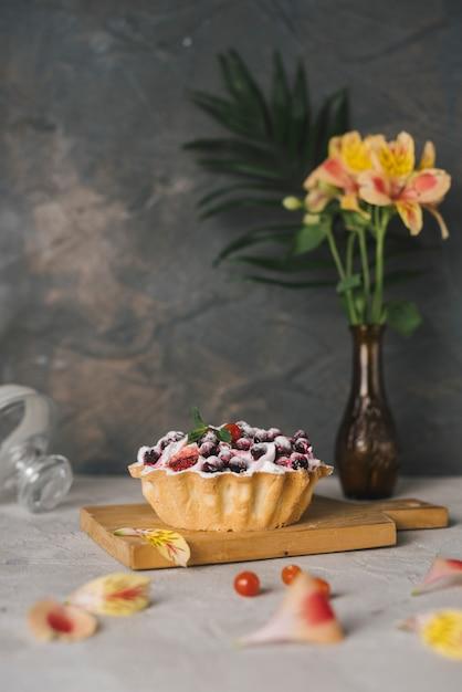 Vase à fleurs alstroemeria près de la tarte aux baies savoureuse sur une planche à découper Photo gratuit