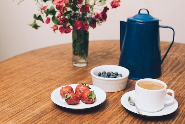 Vase à fleurs; baies et tasse de café sur la table Photo gratuit
