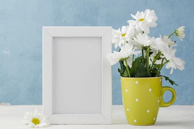 Vase Avec Fleurs à Côté Du Cadre Photo gratuit
