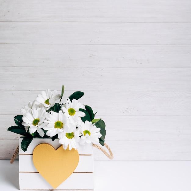 Vase à fleurs décoratif blanc magnifique avec forme de coeur sur fond en bois Photo gratuit