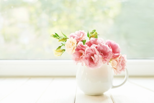 Vase avec des fleurs d'eustoma sur une table contre une fenêtre Photo Premium