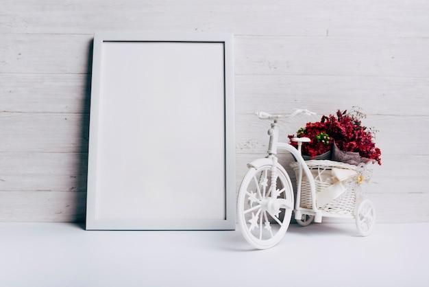 Vase à fleurs avec vélo près du cadre blanc sur le bureau Photo gratuit