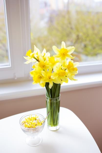 Vase avec des jonquilles jaune vif sur une table en bois blanche Photo Premium