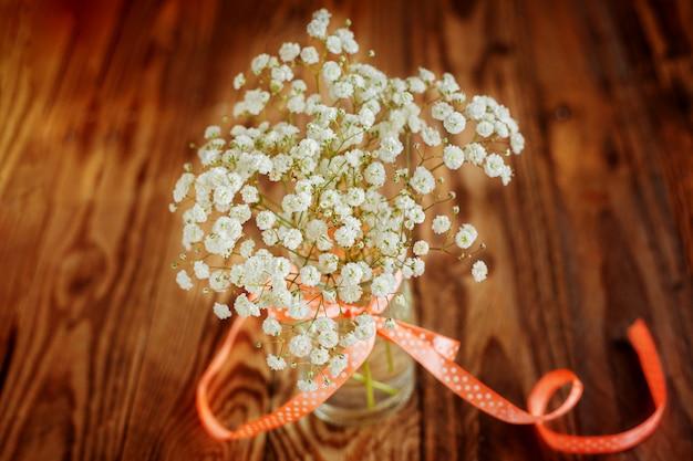 Vase Avec Ruban Et Bouquet De Gypsophile (fleurs De Souffle De Bébé) Sur Table En Bois Photo Premium