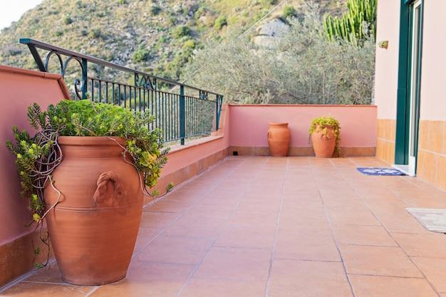 Des vases en céramique pour l'huile d'olive ornent les balcons en sicile. Photo Premium