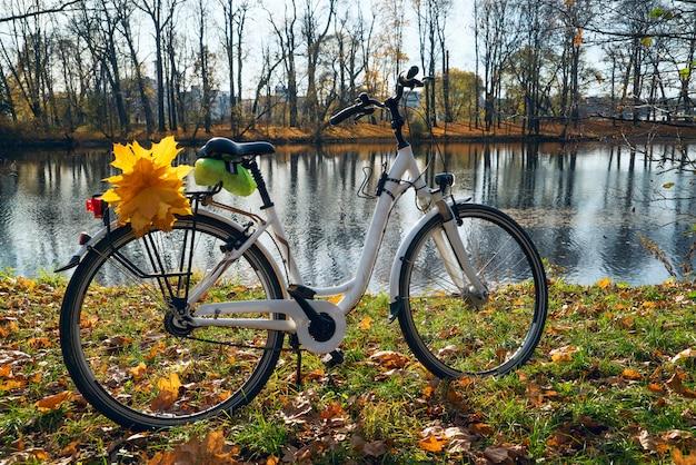 Vélo blanc avec des feuilles jaunes sur le coffre Photo Premium