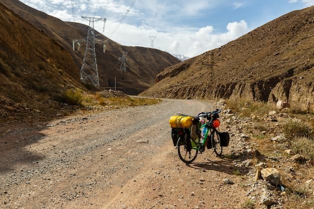 Vélo Du Voyageur Avec Des Sacs Se Tenir Sur La Route De Montagne, Rivière Kokemeren, Kirghizistan, Vélo De Tourisme Photo Premium