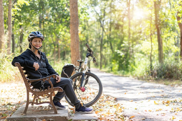 Vélo Femme Asiatique Senior Avec Assis Dans Le Parc Photo Premium