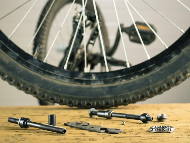 Vélo de montagne à roue arrière et outils sur une table en bois. Photo Premium