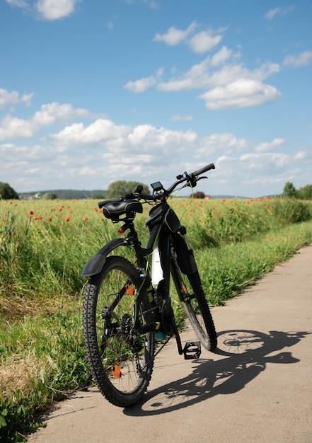 Un vélo à propulsion électrique se dresse sur un chemin de pierre à côté du champ vert printanier avec des coquelicots rouges Photo Premium