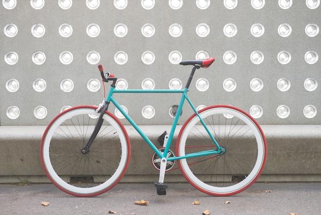 Un vélo de ville fixe engrenage sur un mur vert et blanc Photo Premium