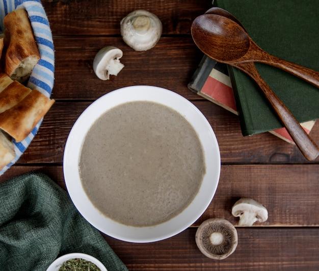 Velouté de champignons dans un bol blanc servi avec du pain, vire top Photo gratuit