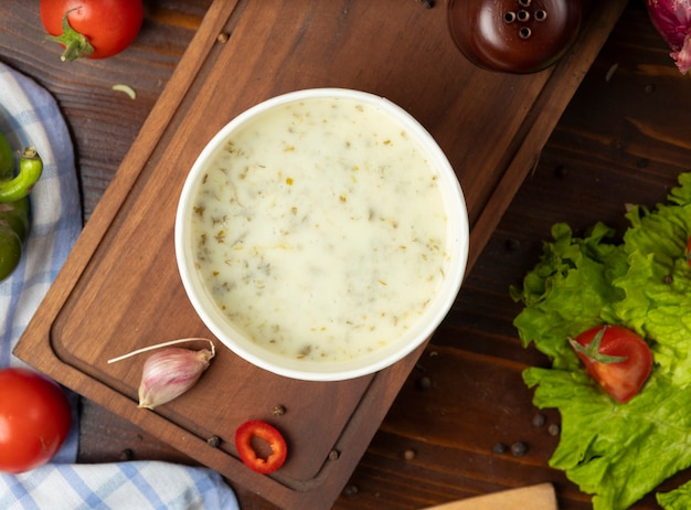 Velouté de champignons dans un bol en coupe jetable servi avec des légumes verts. Photo gratuit