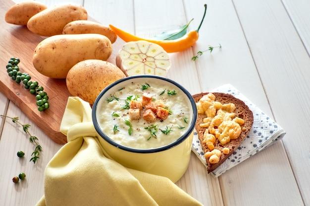 Velouté de pommes de terre avec croûtons, servi avec du pain grillé au fromage Photo Premium