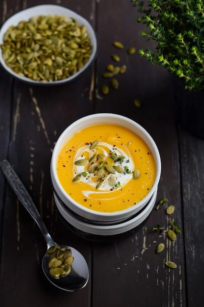 Velouté De Potiron à La Crème Et Graines De Citrouille Sur Une Table En Bois. Photo Premium