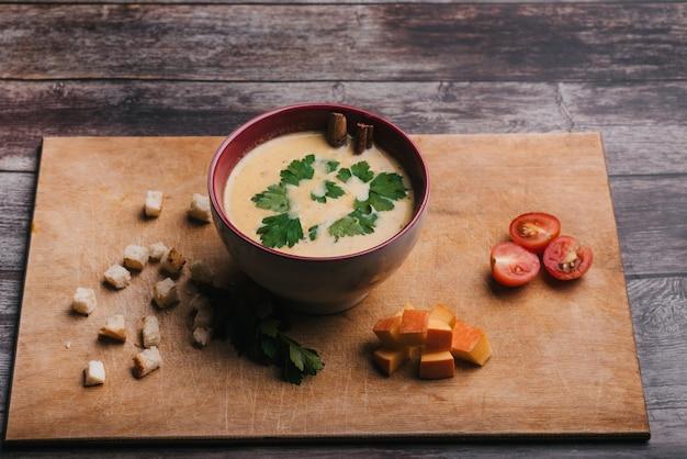 Velouté de potiron dans un bol avec du persil sur une table en bois avec des craquelins et des tomates. nourriture d'automne traditionnelle pour halloween Photo Premium