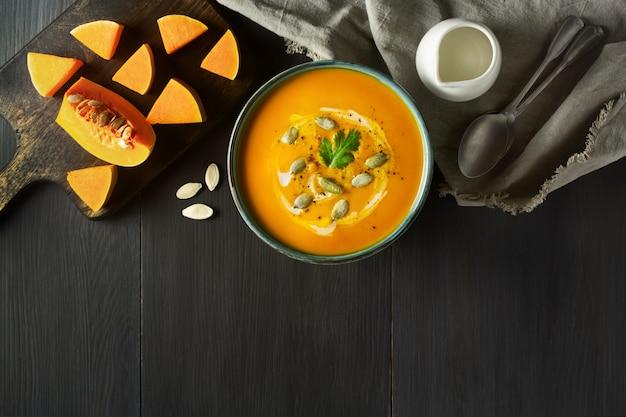 Velouté de potiron dans un bol avec des tranches de potiron, persil, crème et citrouille sur une table en bois Photo Premium