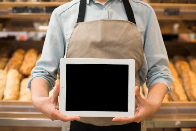 Vendeur de boulangerie debout montrant des tablettes différentes pâtisseries Photo gratuit