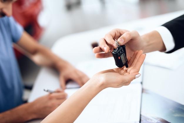 Le vendeur dans la salle d'exposition remet les clés de la voiture à l'acheteur. Photo Premium