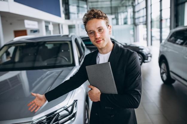 Vendeur dans un showroom automobile Photo gratuit