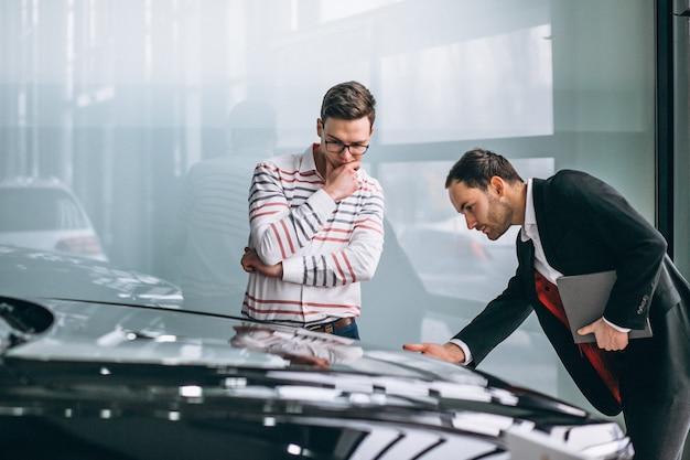 Vendeur dans un showroom de voitures vendant une voiture Photo gratuit