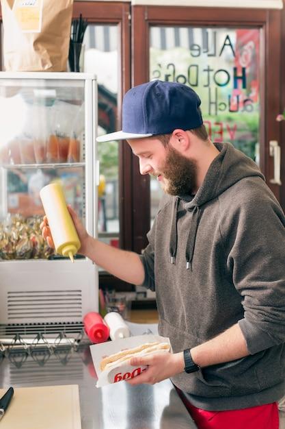 Vendeur faisant hot-dog au fast food snack bar Photo Premium