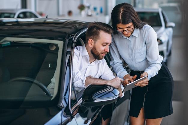 Vendeur et femme à la recherche d'une voiture dans une salle d'exposition Photo gratuit