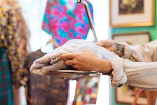 Vendeur masculin vérifiant le poids du tissu sur des balances au magasin de vêtements Photo gratuit