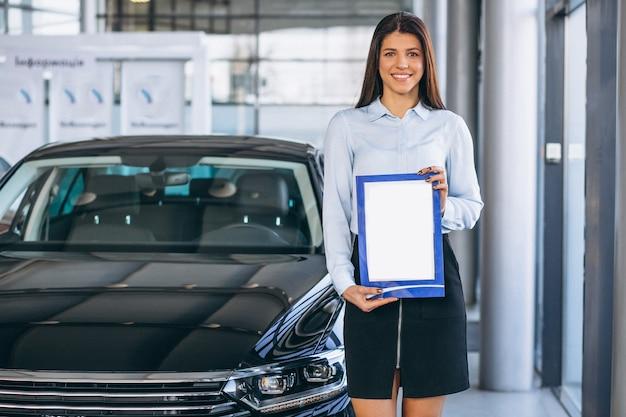 Vendeuse dans un showroom automobile Photo gratuit
