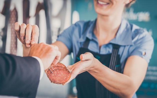 Vendeuse donnant de la viande au client Photo Premium