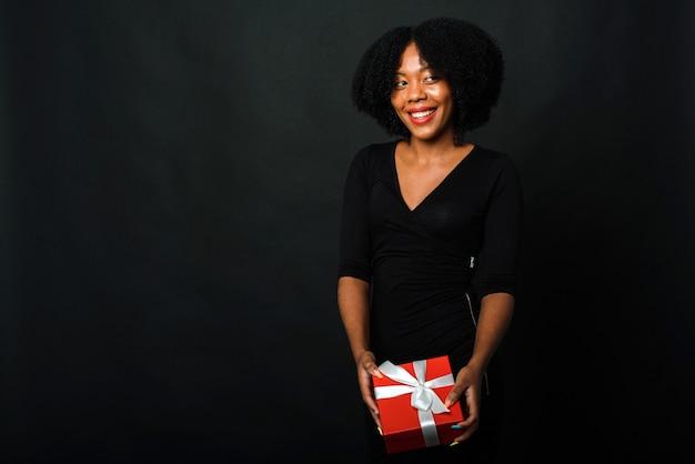 Vendredi Noir. Une Femme à La Peau Sombre Tient Un Cadeau Du Nouvel An Dans Ses Mains Sur Un Fond Noir Photo Premium