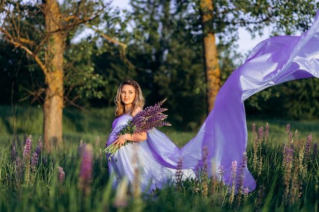 Vent souffle la robe violette d'une femme enceinte alors qu'elle se tient dans le champ de lavande Photo gratuit
