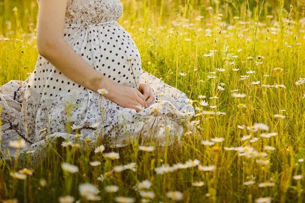 Ventre de femme enceinte dans la nature. jeune fille enceinte au coucher du soleil, femme enceinte se détendre à l'extérieur dans le parc Photo Premium