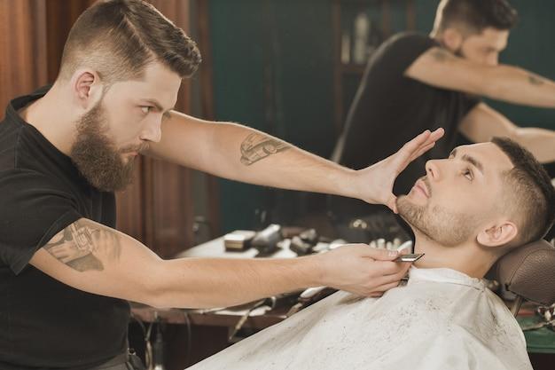 Vérifier son travail. coiffeur professionnel vérifiant sa barbe coupée donnée au client Photo Premium