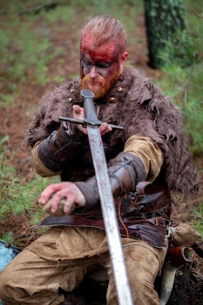Véritable viking affilant son épée avec une pierre Photo Premium